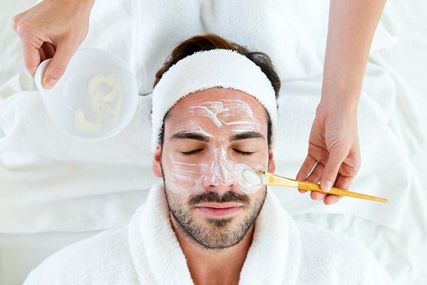 Portrait of man with clay facial mask in beauty spa.